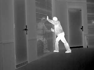 White hot thermal image of a man breaking into a warehouse