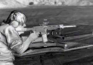 A thermal image of a man firing a rifle with a thermal rifle scope mounted on his weapon