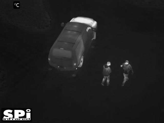White hot thermal UAV drone image of people by a car